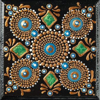 Художественная роспись в виде точек мандалы на деревянной плитке. красивая мандала, нарисованная вручную красочными точками на черном дереве.