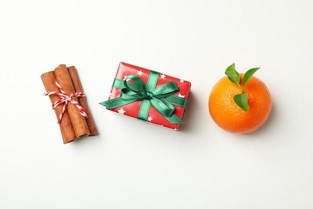 Мандарин, корица и подарочная коробка на белом