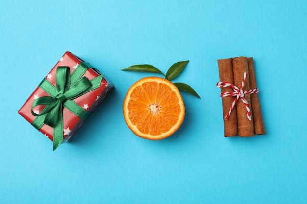 Mandarin, cinnamon and gift box on blue