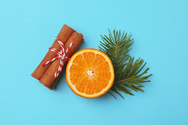 Mandarin, cinnamon and pine branch on blue