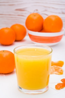 Mandarin juice in a glass and ripe mandarins on a table
