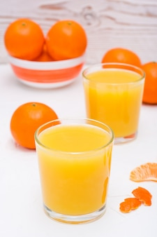 Mandarin juice in a glass and slices of tangerines on a table