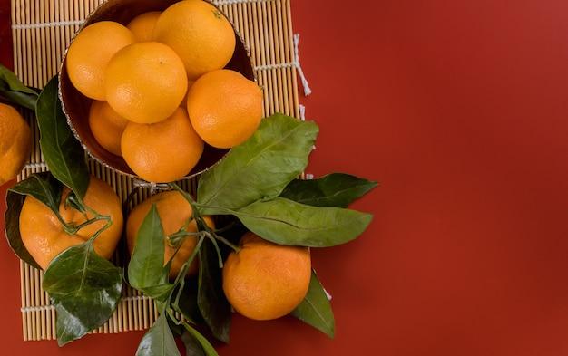 マンダリンオレンジ、緑の葉、バスケット、赤