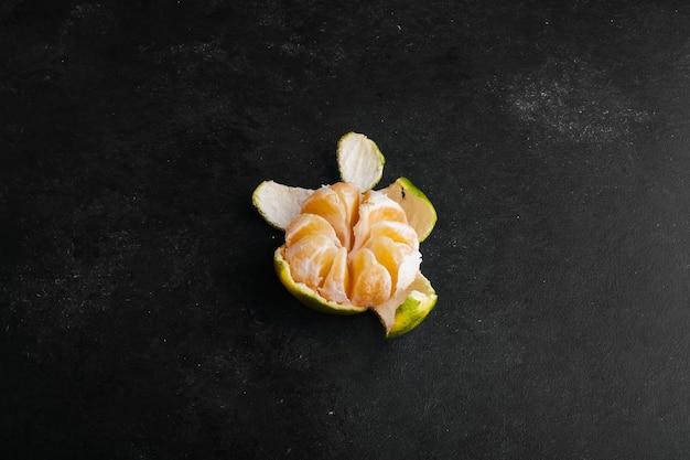 Mandarino con buccia verde sbucciata.