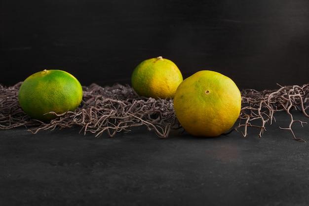 Mandarin oranges on black background .