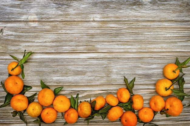 Mandarin oranges with leaves on rustic wood