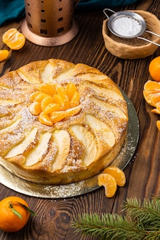 Mandarin pie and tangerines on rustic wood background