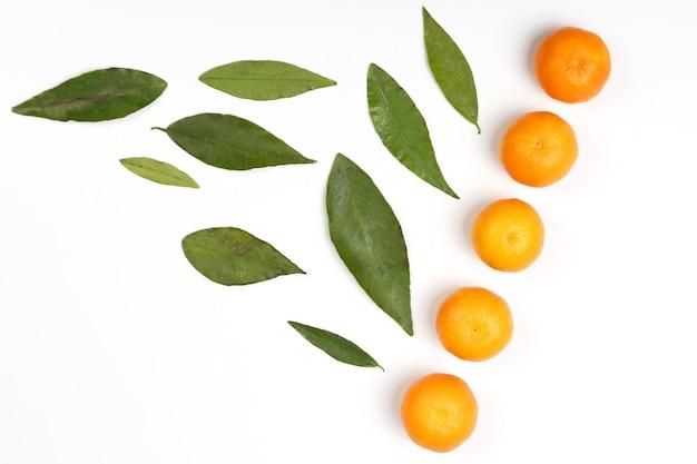 白い背景の葉とみかん。健康的な新鮮な野菜と食品