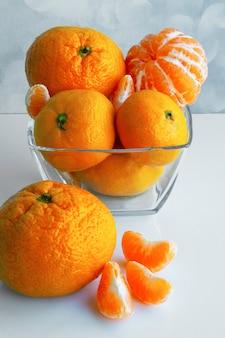 흰색 테이블에 만다린 오렌지 또는 귤. 유리 그릇에 귤입니다. 귤 조각. 감귤류