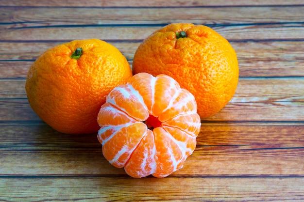 나무 테이블에 만다린 오렌지 또는 귤. 피부에 있는 귤과 피부에 없는 귤. 감귤류