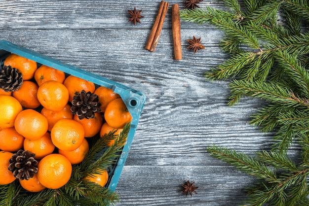 Мандарины на деревянных с рождественскими еловыми ветками