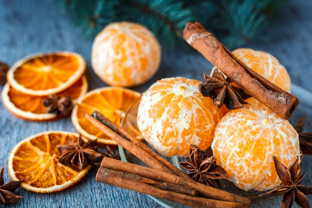Mandarins, dried oranges, anise and cinnamon sticks on a wooden table next to the fir branch