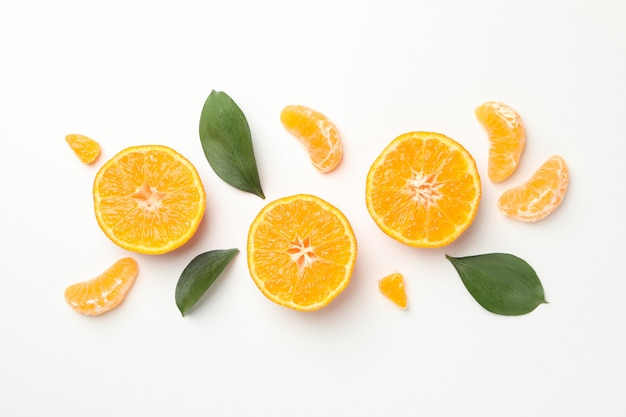 Mandarins and leaves on white background, top view