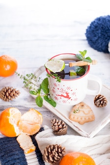 Mandarins and tea in a white mug with a deer. knitted winter scarf and a white cap with a blue strip on a white wooden background. copy space for text happy new year greeting card winter theme