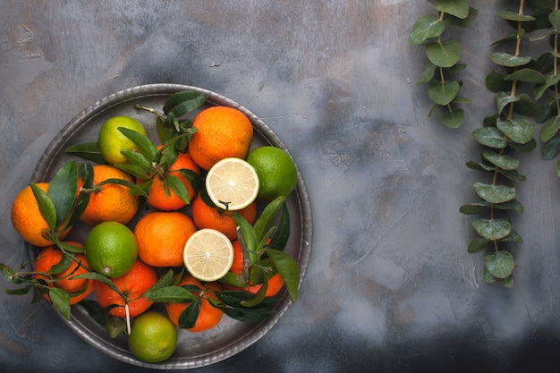 Mandarins with green leaves on a metal plate, on a gray background