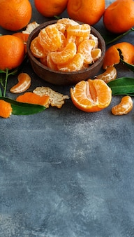 Mandarins with leaves in a bowl on a grey  background