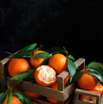Mandarins with leaves in a box on a dark background