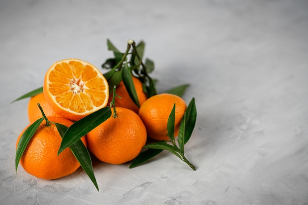 Mandarins with leaves on the grey concrete background.