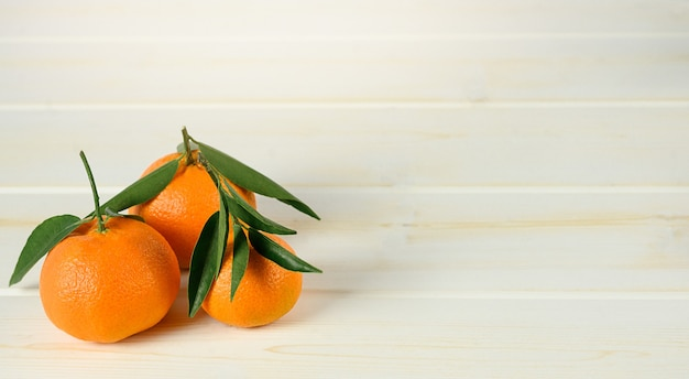 Mandarins with leaves on the white wooden background.