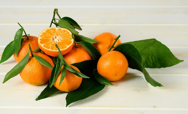 Mandarins with leaves on the white wooden table.