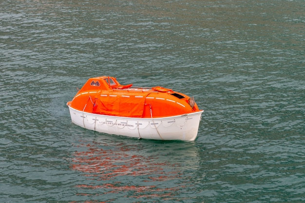 Maneuvering orange lifeboat in water in arctic waters, svalbard. abandon ship drill. lifeboat training. man over board drill.