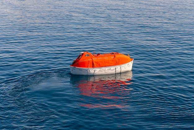 Maneuvering orange lifeboat in water in arctic waters