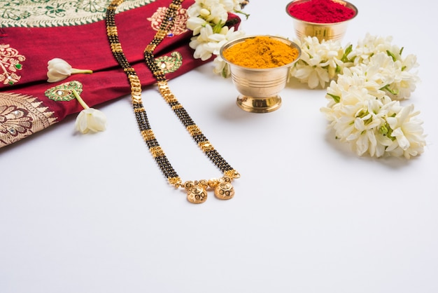 Mangalsutra or golden necklace to worn by a married hindu women, arranged with traditional saree  with huldi kumkum and mogra flowers gajra, selective focus
