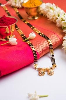 Мангалсутра или золотое ожерелье для замужних индуистских женщин, украшенное традиционным сари с хульди кумкум и цветами могры гаджра, выборочный фокус