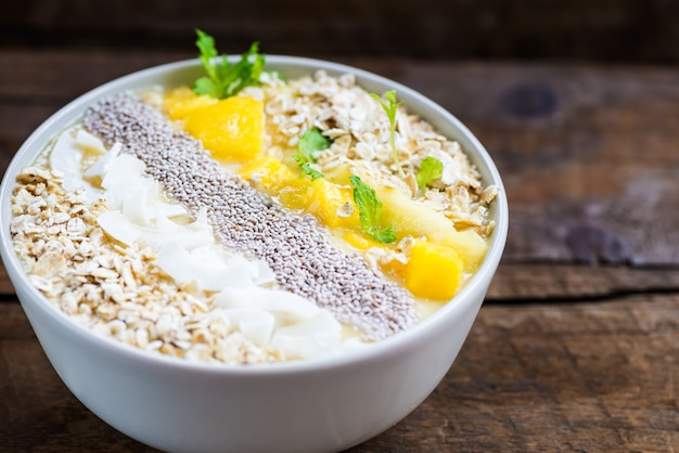 Mango, banana, pineapple and oatmeal smoothie in the bowl