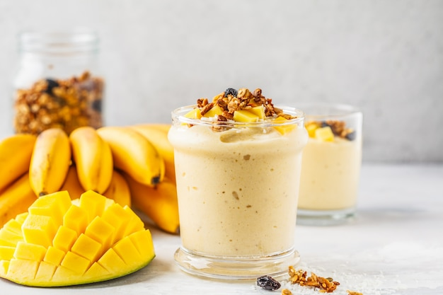 Mango banana smoothie with granola and coconut in a jar. plant based food concept.