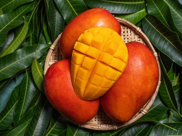 Mango in a basket on green leaf background