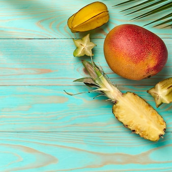 コピースペースと青い木製の背景にマンゴー、ゴレンシ、パイナップル、パームグリーンの葉。トロピカルフルーツ。フラットレイ