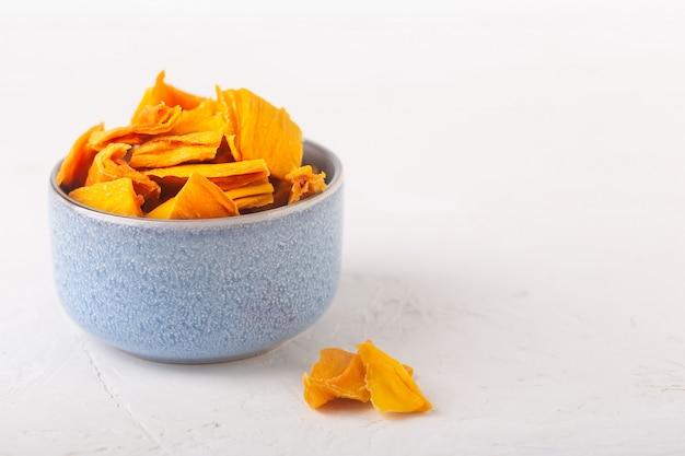 Чипсы манго в синей миске и кусочки этих фруктов на столе