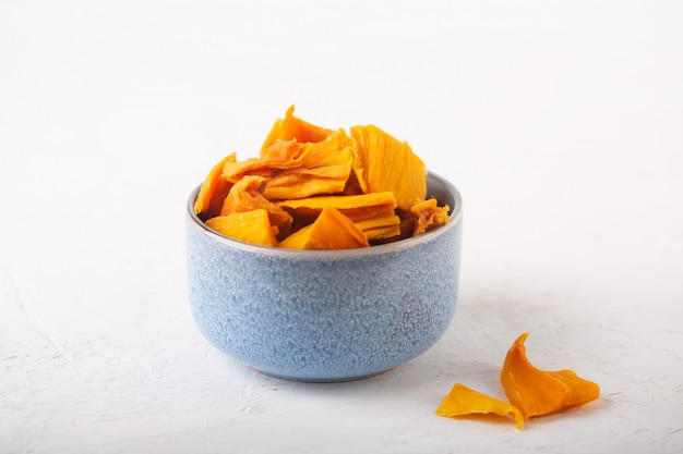 Манго чипсы в синей миске на белом фоне