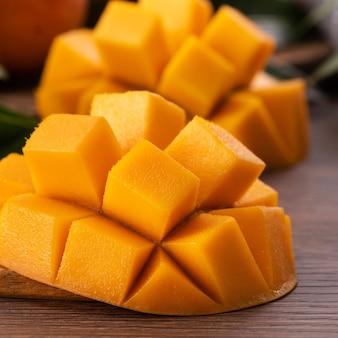 マンゴー。緑の葉と暗い木製のテーブルの背景の上に葉と新鮮な熟したマンゴーフルーツのクローズアップ。