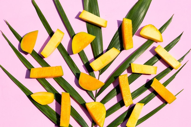Mango cut pieces on palm tree leaves on pink background. top view