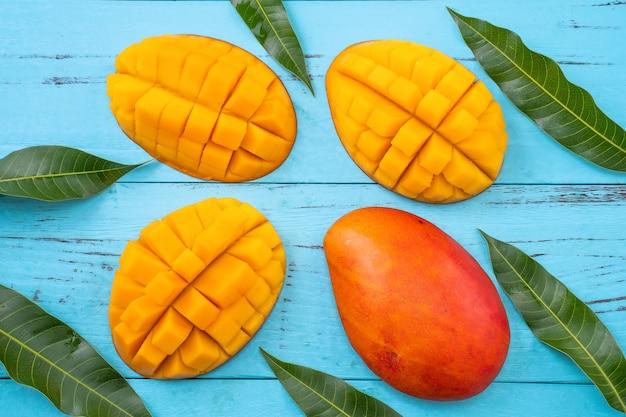 マンゴー-明るく鮮やかな水色の木製テーブルの背景、上面図、フラットレイレイアウト、オーバーヘッドショットで分離された新鮮なみじん切りのトロピカルマンゴーフルーツ。