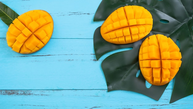 Манго - свежие нарезанные плоды тропического манго, изолированные на ярко-ярком голубом фоне деревянного стола, вид сверху, плоская планировка, съемка сверху.