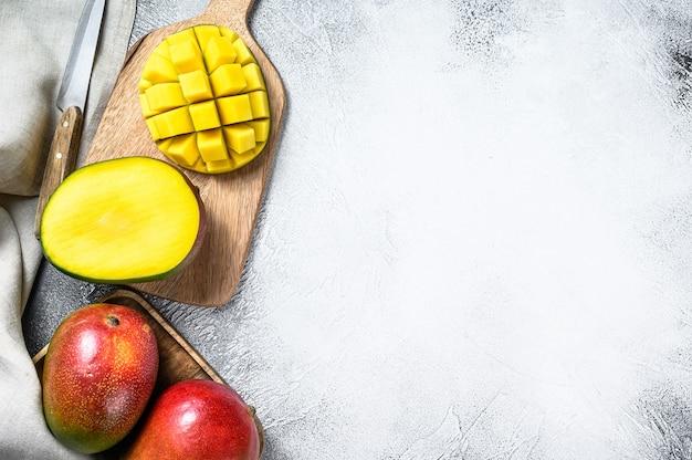 Плоды манго нарезать кубиками на разделочной доске. серый фон