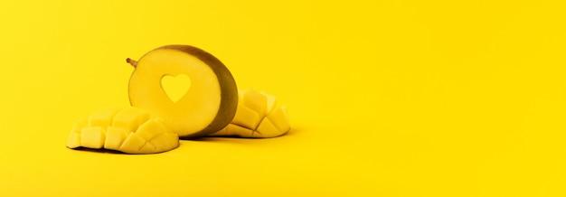 Плоды манго с нарезанным сердцем манго на желтом фоне, панорамное изображение, любовь к экзотическим фруктам.
