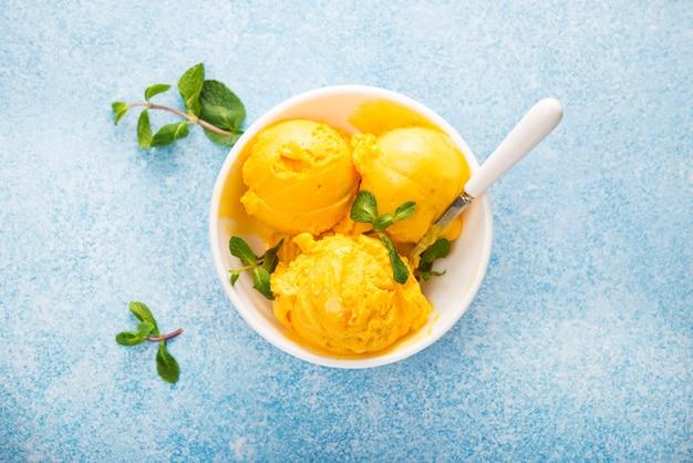 Мороженое из манго, сорбет в тарелке на бетонном фоне, вид сверху