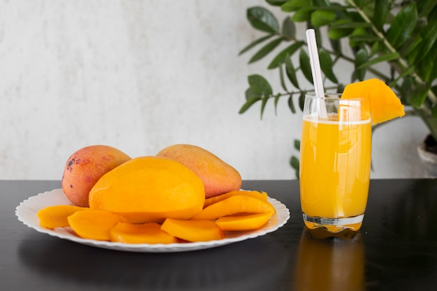The mango is a fruit of varied coloring, native to the south and southeast of asia. photo of mango with a white dish and a glass with mango juice.