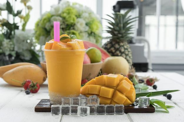 Сок манго и манго на деревянном столе