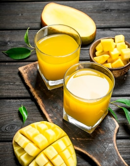Mango juice in a glass on a cutting board.