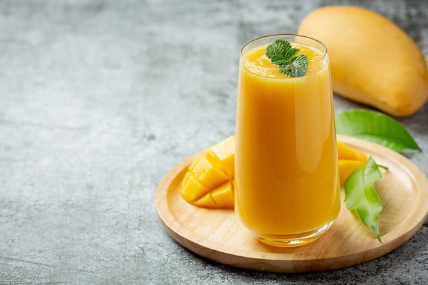 Mango juice in the glass on dark surface
