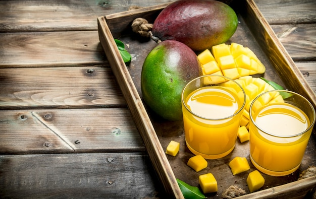 Mango juice in a glass on tray. on wooden table