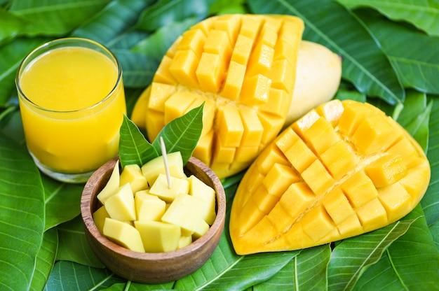 Стакан сока манго с ломтиком манго на листьях манго из дерева. концепция тропических летних фруктов - сладкие спелые манго