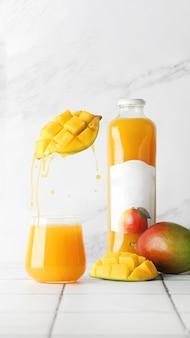 軽いタイルのテーブルの上のガラスのテーブルの上のマンゴージュース。マンゴージュースのスプラッシュ。夏のコンセプト。