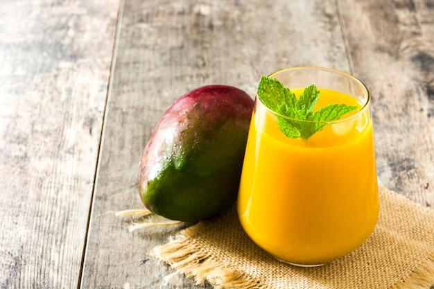 Mango lassi dessert traditional indian drink on wooden table