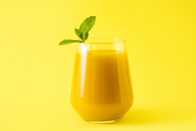 Mango lassi dessert traditional indian drink on yellow background
